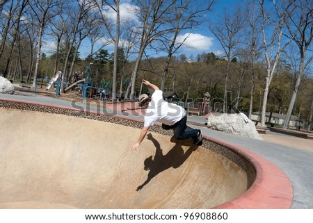 Action shot of a young skateboarder skating sideways against the wall of the bowl at a skate park. - stock photo