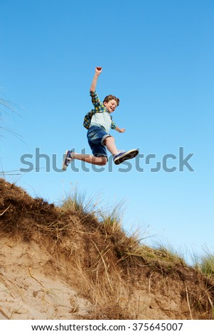 Action Shot Of Boy Jumping From Sand Dune