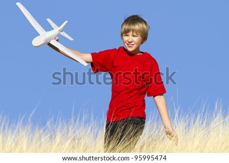 Action shot of boy playing with toy airplane. - stock photo