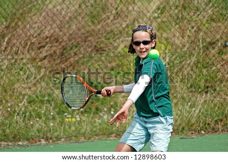 action shot of girl playing tennis - stock photo