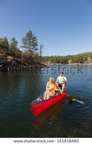 Action Shot of Man and Woman Paddling a Canoe on Beautiful Lake - stock photo