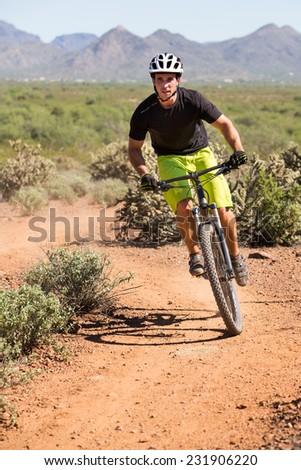 Action Shot of Young Man Biking on Desert Trail - stock photo