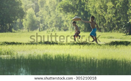Action two children running on the berms, ditches in fields. playfully The life of children a farmer in Thailand. - stock photo