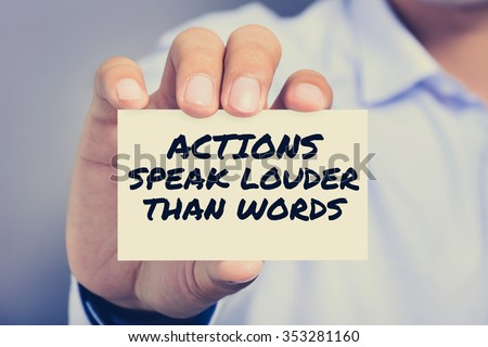 ACTIONS SPEAK LOUDER THAN WORDS, message on the card shown by a man, vintage tone - stock photo