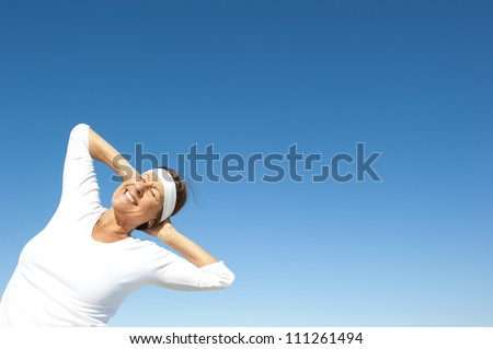 Active and attractive senior woman posing happy and joyful on a sunny day, isolated with blue sky as background and copy space. - stock photo