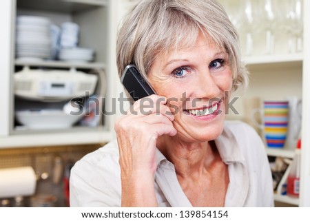 Active attractive senior woman with grey hair talking on the telephone and smilling while standing in her kitchen - stock photo