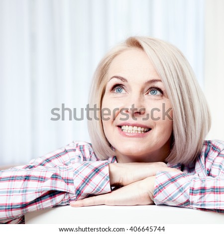 Active beautiful middle-aged woman smiling friendly and looking up at home in the living room. Woman's face close up - stock photo