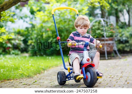 Active blond kid boy driving tricycle or bicycle in domestic garden. Toddler child having fun on warm summer day. Active games for children outdoors. - stock photo