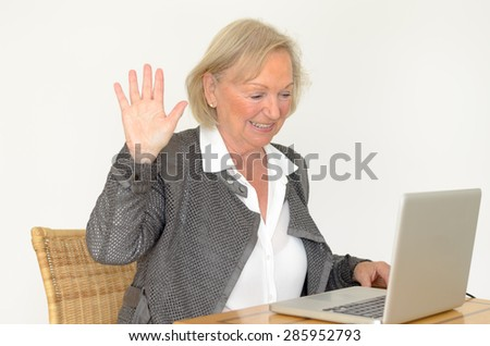 Active blond senior woman with formal clothes and friendly smile showing hand up while sitting at desk in front of a silver laptop