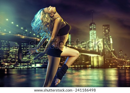 Active blonde beauty on evening city sky background - stock photo
