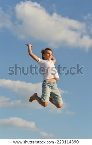 Active boy jumping on blue sky background