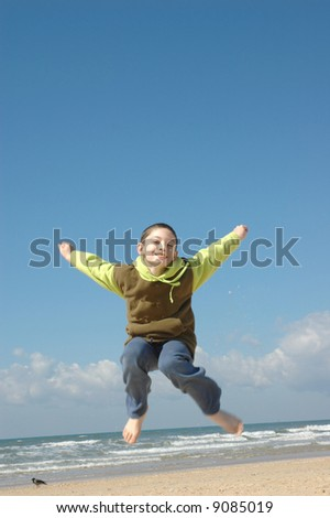 Active boy on the beach on nice winter day - stock photo