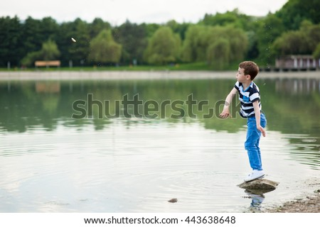 active boy throws small stone into the lake - stock photo