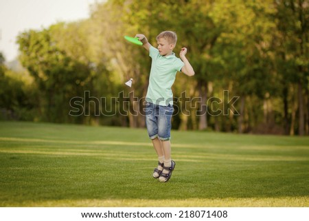 Active boy with racket jumping, playing tennis in the park