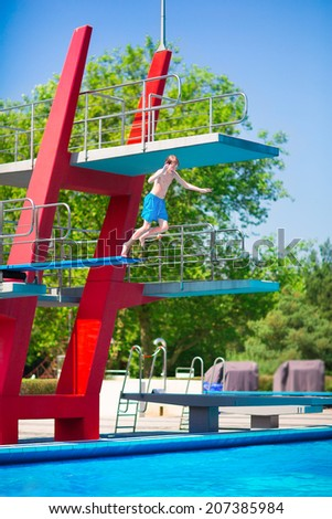 Active brave teenager boy jumping into an outdoor pool from a high tower with spring board learning to dive during sport class on a hot summer day - stock photo