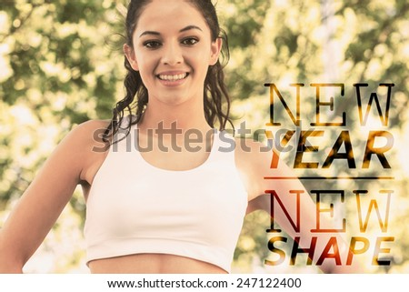 Active cheerful brunette standing hands on hips smiling against new year new shape - stock photo