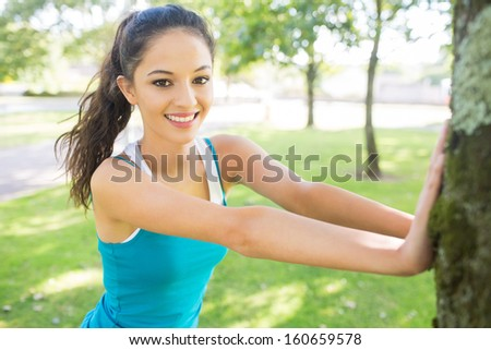 Active cheerful brunette stretching her leg in a park on a sunny day