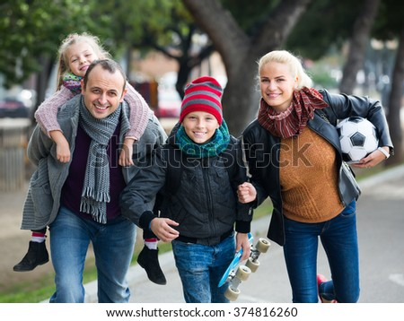 Active cheerful family with two children spending weekend together outdoors - stock photo