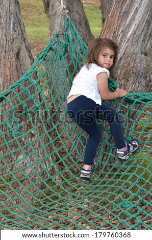 Active child (age 3 - 6 ) climb on a net in the park. concept photo
