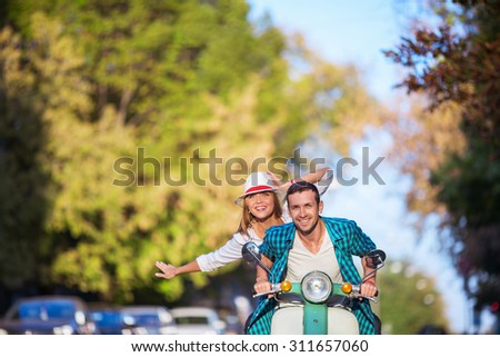 Active couple on a scooter outdoors - stock photo