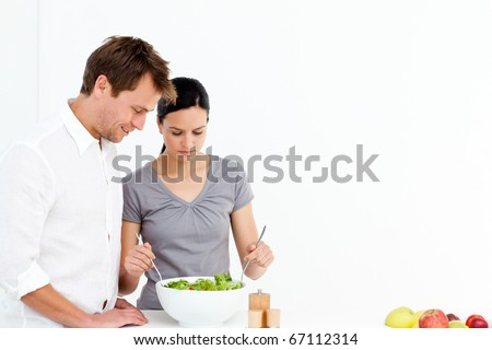 Active couple preparing a salad for lunch in the kitchen