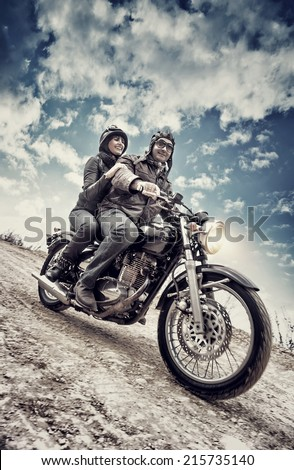 Active couple riding on the motorbike, slow motion, having fun in bikers tour, vintage style photo, happy adventure concept - stock photo