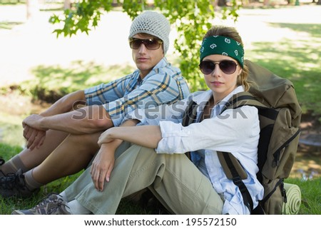 Active couple sitting down on a hike looking at camera on a sunny day - stock photo