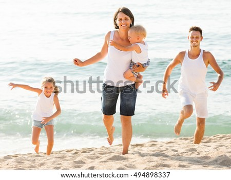 active couple with two children running on beach vacation
