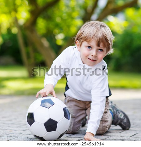 Active cute little kid boy playing soccer and football and having fun, outdoors. Active leisure with children on warm sunny summer day.