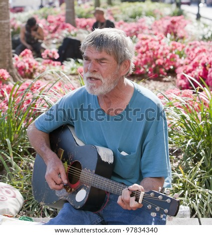 Active elderly man playing guitar outside during the day - stock photo