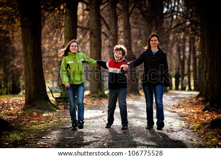 Active family - mother and kids walking outdoor - stock photo