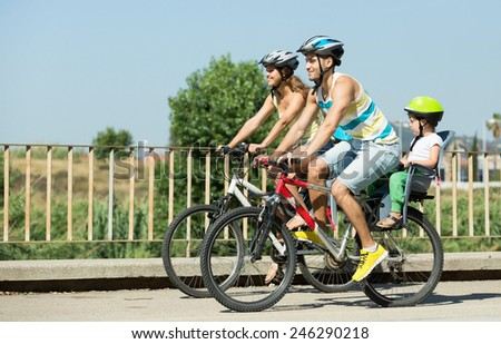 Active family of four cycling on street road in summer day - stock photo