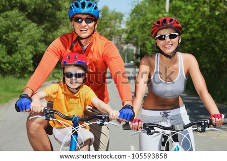 Active family of three riding their bikes in summer