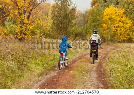 Active family on bikes, cycling outdoors, golden autumn in park, family sport and healthy lifestyle  - stock photo