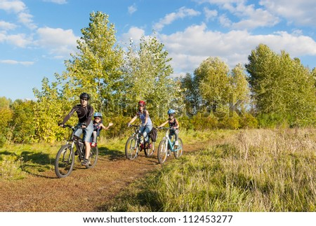 Active family on bikes cycling outdoors. Happy parents with two kids on bicycles. Sport and healthy lifestyle with children, family summer vacation