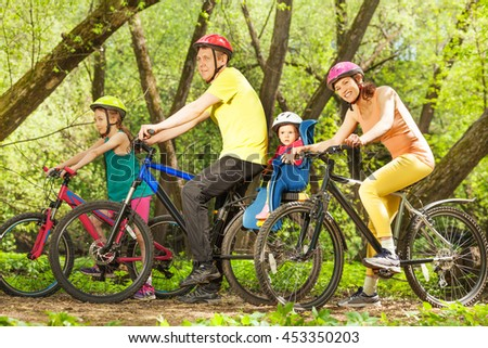 Active family on bikes riding in sunny forest