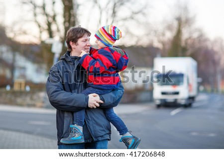 Active father holding his child, little funny kid boy on arm, on cold day. Man and boy walking together in a park in spring, autumn or winter. Happy, joyful family - stock photo