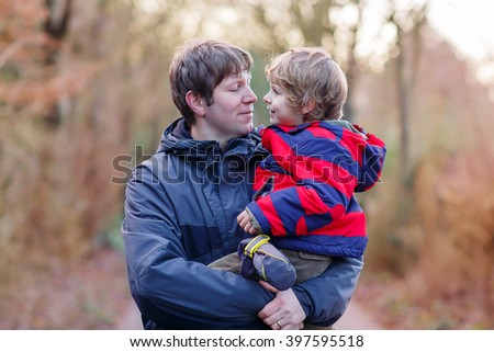 Active father holding his child, little funny kid boy on arm, on cold day, walking together in a park in spring, autumn or winter. Happy, joyful family of two. - stock photo