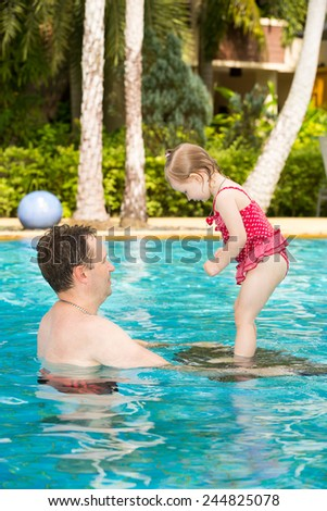Active father teaching his toddler daughter to swim in pool on tropical resort. Summer vacations and sport  concept - stock photo