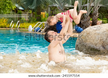 Active father teaching his toddler daughter to swim in pool on tropical resort . Summer vacations and sport  concept