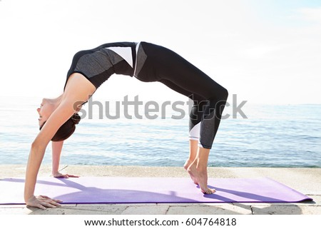 Active female stretching on yoga mat, arching her back bending backwards, with sea in background, nature outdoors. Woman doing sport exercising, body and mind control, conceptual recreation lifestyle.