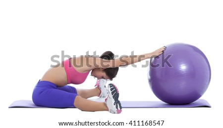 Active fit woman having a break on a swiss ball.