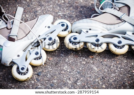 Active fun leisure in spring summer outdoor activities concept. Closeup roller skates on asphalt. - stock photo