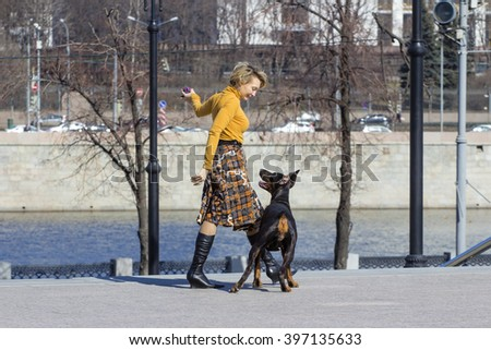 Active game. Woman playing with big female dobermann dog
