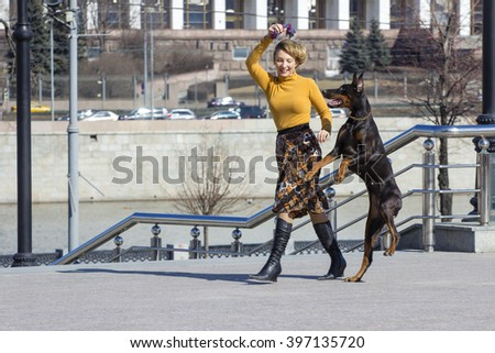 Active game. Woman playing with big female dobermann dog - stock photo