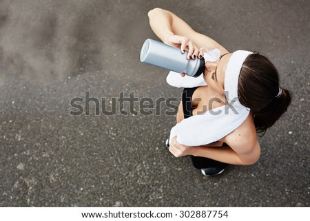 Active girl drinking water after workout - stock photo