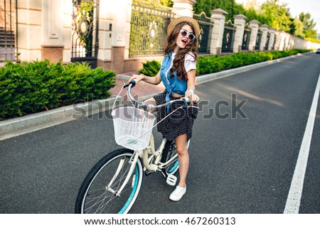 Active girl with long curly hair in hat  driving a bike on road. She wears long skirt, jerkin, blue sunglasses. She has fun to camera.