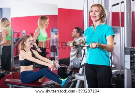 Active glad smiling people  weightlifting training in modern health club