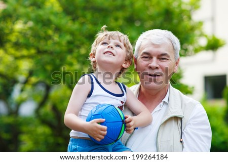 Active grandfather playing with little grandson ball in summer