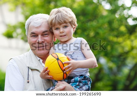 Active grandfather playing with little grandson ball in summer - stock photo